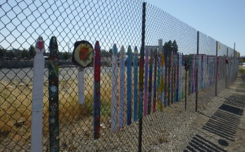 Decorated fence boards with the grain elevator in the distance.